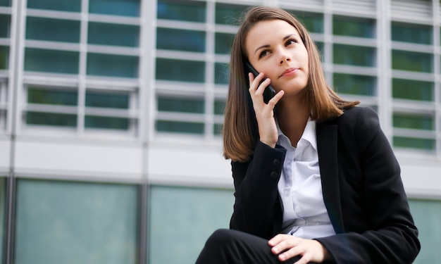 Portrait of a young woman talking on the phone sitting on a bench outdoor
