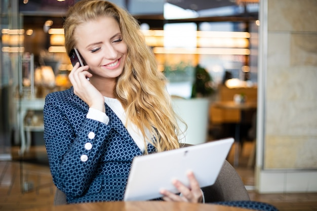 Portrait of a young woman talking on the phone and using a digital tablet on a break