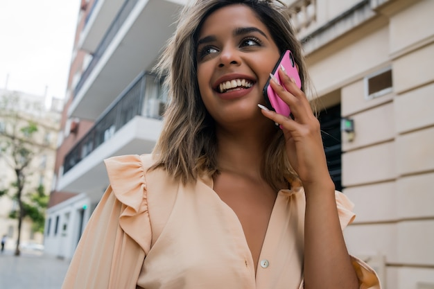 Portrait of young woman talking on the phone while standing outdoors on the street