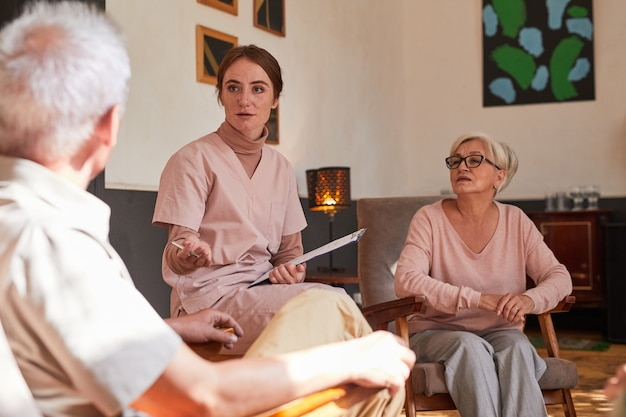 Portrait of young woman talking to senior people at retirement home during therapy session