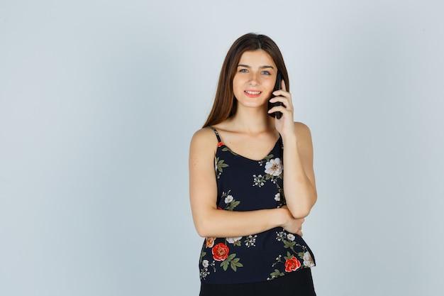 Ritratto di giovane donna che parla su smartphone in camicetta, gonna e sembra allegra vista frontale