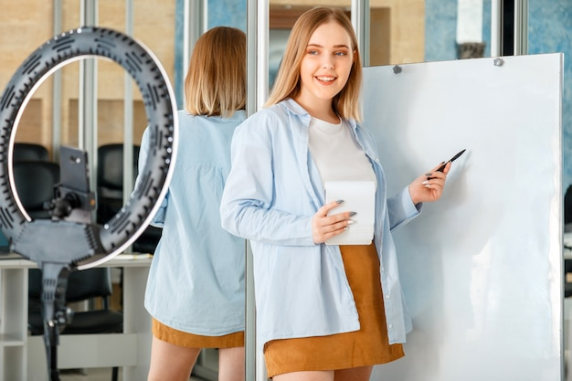 Portrait of young woman teacher or blogger influencer near whiteboard in empty classroom recording live online training presentation using circular lamp smartphone. elearning webinar in university.