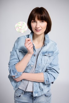 Portrait of young woman or teenage girl with braces on teeth holding lollipop over gray background