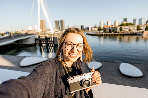 Portrait of a young woman tourist standing on the beautiful morning cityscape background in rotterdam city