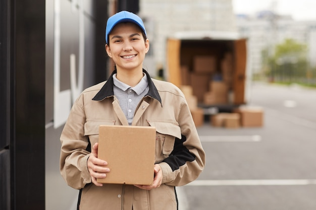 Portrait of young woman in uniform holding parcel and smiling at camera while standing near the warehouse