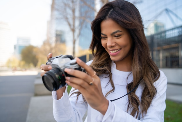 Portrait of young woman using camera while taking photographs in the city. new normal lifestyle concept.