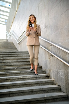 Portrait of a young woman using her smartphone on stairs outdoor