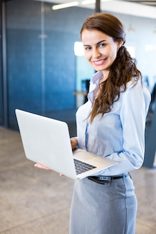 Portrait of young woman using laptop in front of conference room in office
