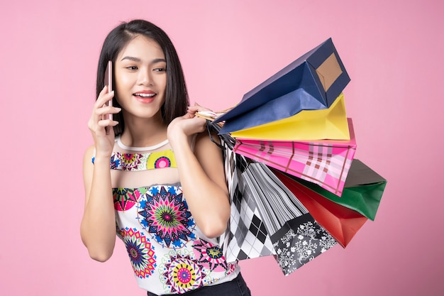 Portrait of young woman using mobile and carrying colorful shopping bags with smile