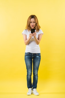 Portrait of a young woman using mobile phone against yellow background