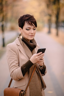 Portrait of young woman using phone on street