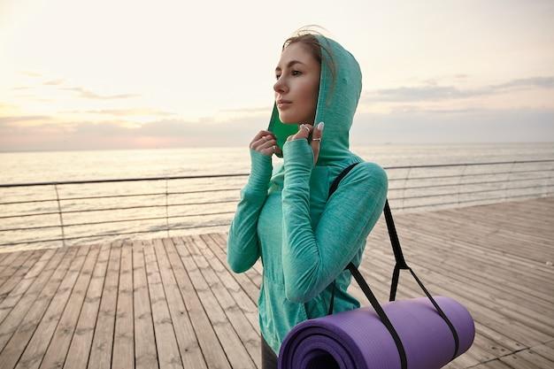 Ritratto di giovane donna che cammina in riva al mare in abiti sportivi luminosi, andando a praticare yoga e fa stretching mattutino.