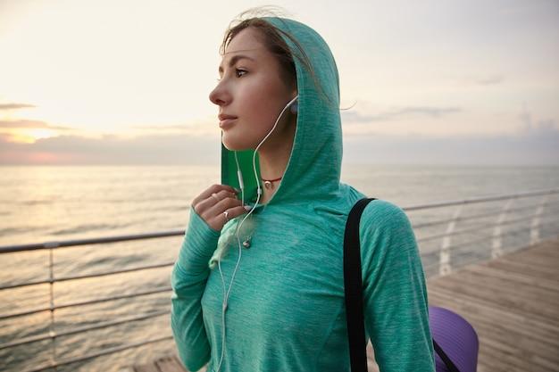 Ritratto di giovane donna che cammina in riva al mare, andando a praticare yoga e fa stretching mattutino.