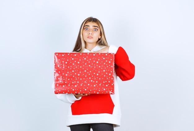 Ritratto di giovane donna con un maglione caldo che tiene il regalo di natale
