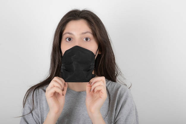 Portrait of young woman wearing black face mask on white.