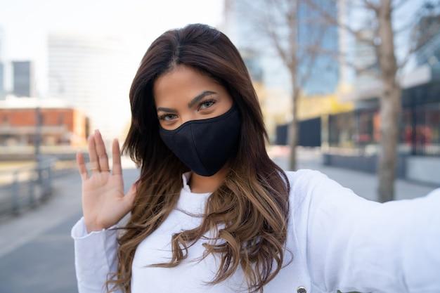 Ritratto di giovane donna che indossa la maschera per il viso e prendendo selfie mentre agita la mano per dire ciao all'aperto. concetto urbano. nuovo concetto di stile di vita normale.