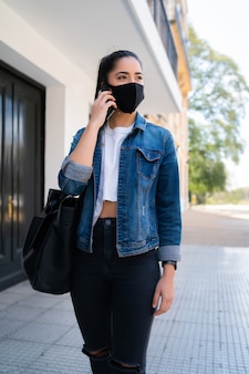 Portrait of young woman wearing face mask and talking on the phone while standing outdoors on the street. urban concept. new normal lifestyle concept.