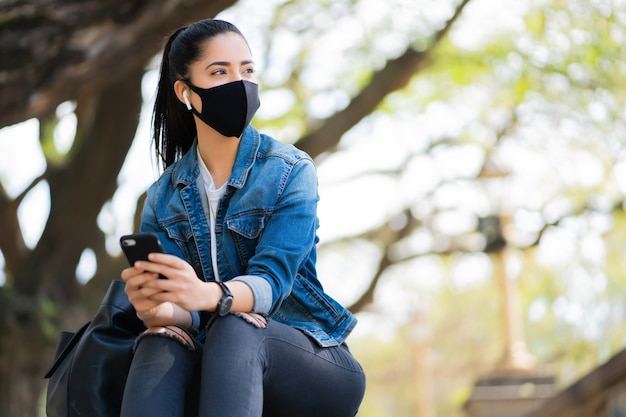 Portrait of young woman wearing face mask and using her mobile phone while sitting on stairs outdoors. new normal lifestyle concept