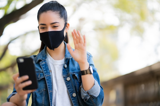 Portrait of young woman wearing face mask on a video call with her mobile phone outdoors.