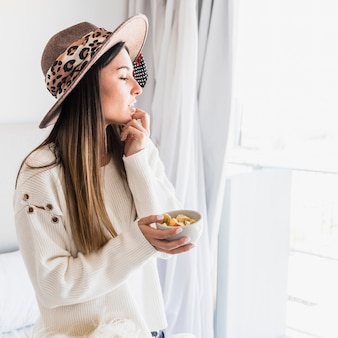 Portrait of young woman wearing hat holding fruit salad bowl looking away