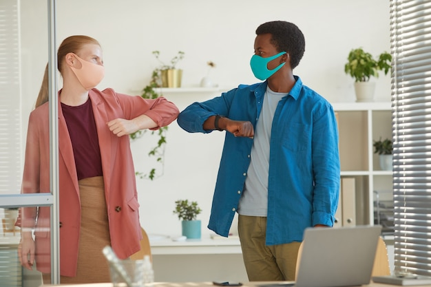 Portrait of young woman wearing mask bumping elbows with african-american colleague as contactless greeting while working in post pandemic office