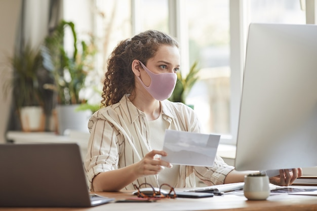 Portrait of young woman wearing mask in office while working at desk and using pc, copy space