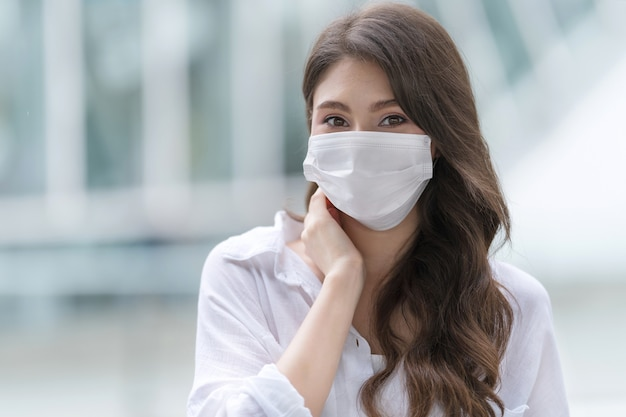 Portrait of young woman wearing medical face mask protective in a city