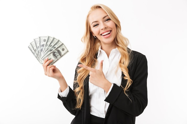 Portrait of young woman wearing office clothing holding fan of money, isolated