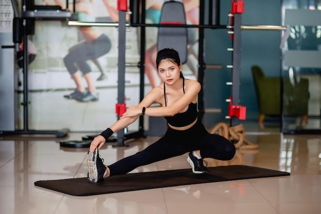 운동복과 스마트 워치를 입고 세로 젊은 여자가 바닥에 앉아 피트니스 체육관에서 운동하기 전에 그녀의 다리와 팔 근육을 streching,