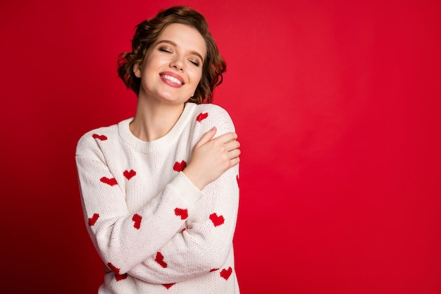 Portrait of a young woman wearing stylish trendy jumper isolated on red wall