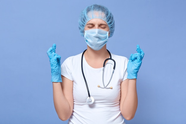 Portrait of young woman wears disposable hat, gloves, medical mask, poses with fingers crossing