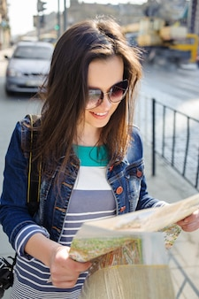 Portrait of a young woman which looks at a map in lviv old city center in ukraine