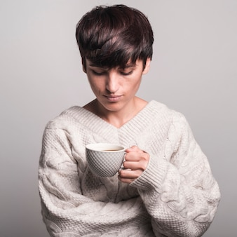Portrait of young woman in white sweater looking at coffee cup