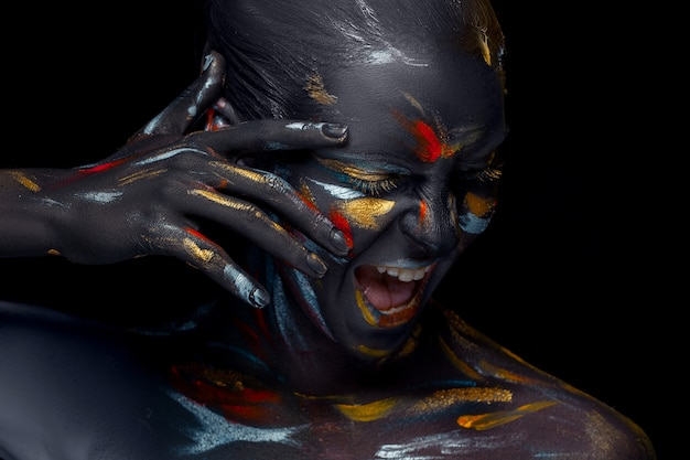 Portrait of a young woman who is posing covered with  black paint