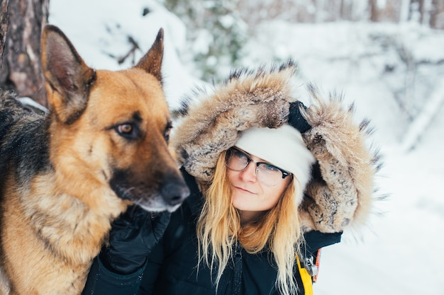 Portrait of young woman in winter coat with dog