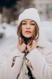 Portrait of young woman in winter outfit outside the street