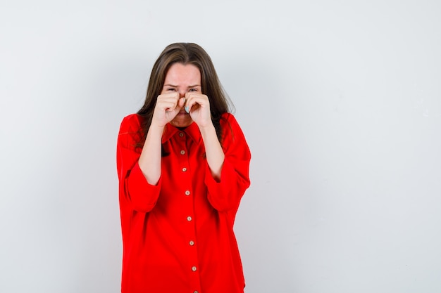 Portrait of young woman wiping her tears with hands in red blouse and looking depressed front view