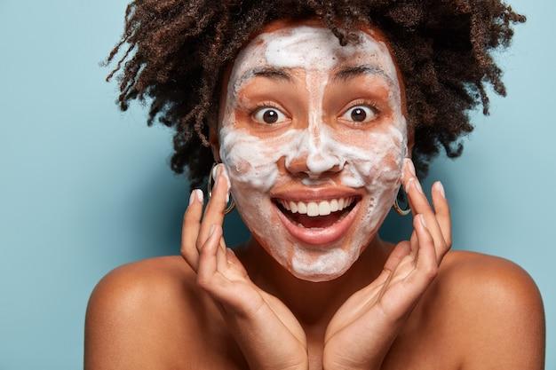 Ritratto di giovane donna con taglio di capelli afro che lava la sua pelle