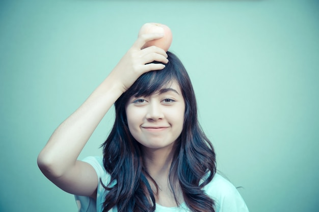 Portrait of young woman with apple on head. concept for healthy care