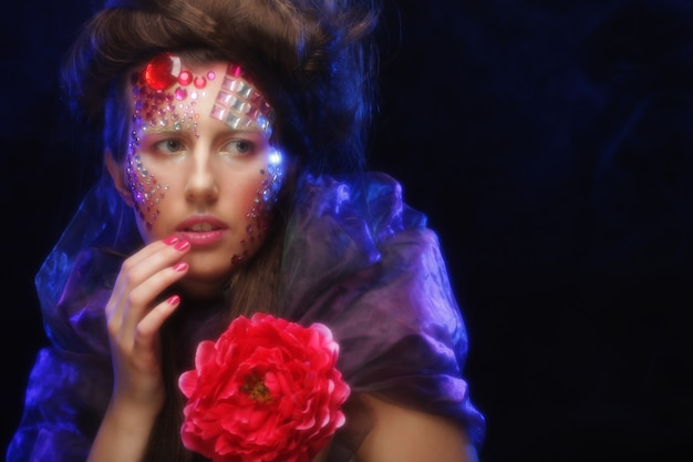 Portrait of young woman with artistic visage holding big red flower