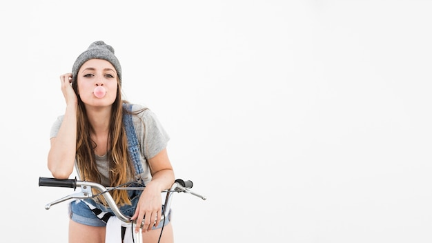 Portrait of a young woman with bicycle blowing bubble on white background