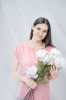 Portrait of a young woman with a bouquet of peonies.