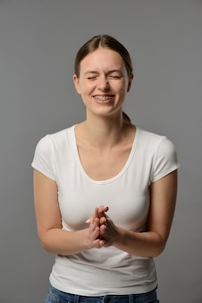 Portrait of a young woman with braces in a white t-shirt