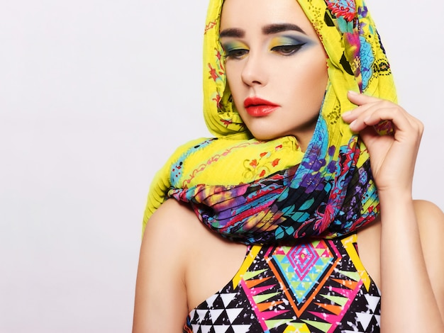 Portrait of a young woman with bright makeup and a fashionable head scarf on a light background