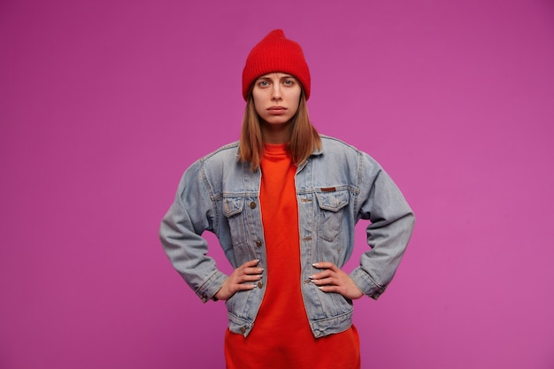 Portrait of young woman with brunette long hair. wearing jeans jacket, red sweater and hat. holds hands on a waist, frown isolated over purple wall