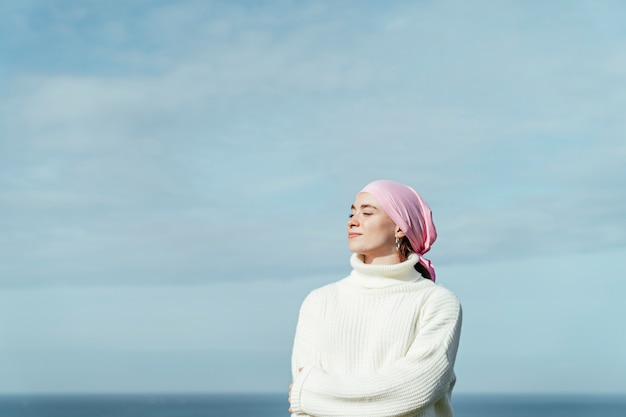 Portrait of young woman with cancer and crossed arms with closed eyes and sky on background