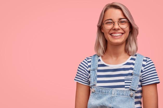 Ritratto di giovane donna con i capelli colorati che indossa una tuta