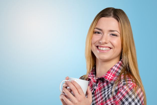 Portrait of a young woman with cup of tea or coffee