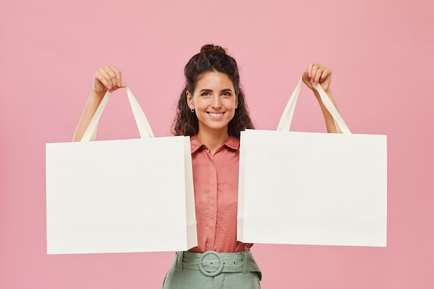 Portrait of young woman with curly hair holding shopping bags and smiling isolated on pink background