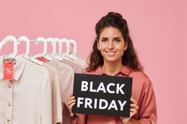 Portrait of young woman with curly hair holding sign with black friday while standing in the shop
